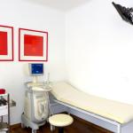 Geräte, Liegebett in einer Frauenarzt-Ordination und ein Monitor an der Wand