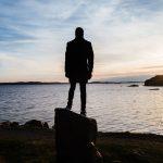 Manns teht auf Felsen und blickt ind en Sonnenuntergang vor dem Wasser