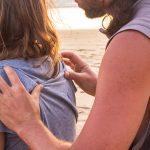Mann massiert Frau am Strand