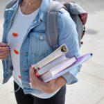 eine studentin mit mehreren büchern unter dem arm